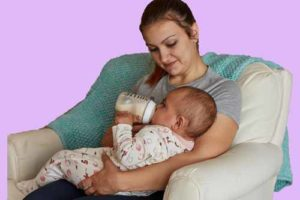 A baby is bottle feeding by a mom a mo